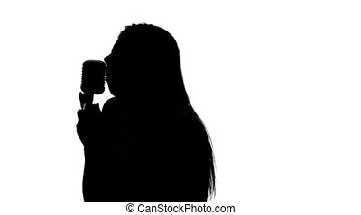 Singer leads to a counter with a microphone. Close up. Silhouette. White