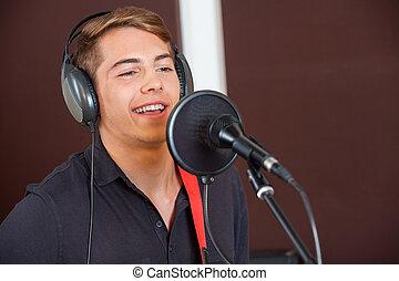 Singer Performing While Looking Away In Studio - Handsome...