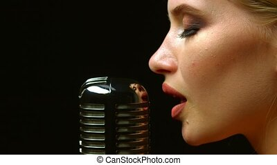 Singer performs songs in a retro microphone. Black...