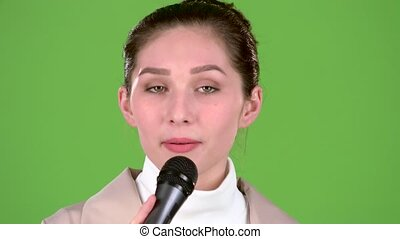 Singer sings a cheerful and melodic song in a spacious concert hall. Green screen
