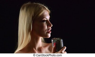 Singer sings in a retro microphone. Black background. Close...