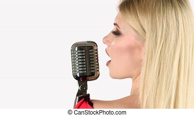 Singer sings in a retro microphone. White background. Side...