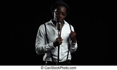 Singer sings into a retro microphone spinning and dancing around him. Black background. Slow motion