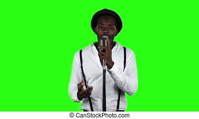 Singer sings into a retro microphone spinning and dancing around him. Green screen. Slow motion