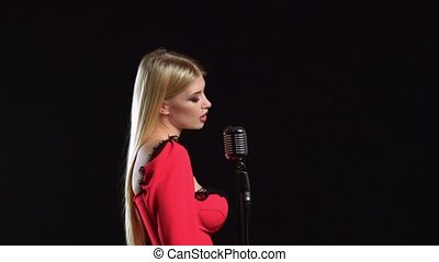 Singer sings songs for the clip. Black background. Side view...