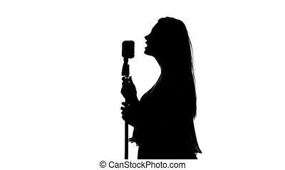 Singer sings the song with a microphone. White. Silhouette