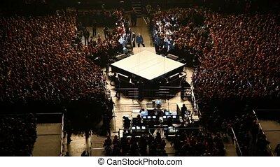 singer stand on scene among spectators in concert hall