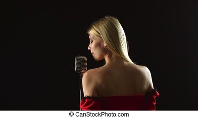 Singer stands with her back to the audience and sings. Black...