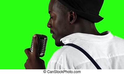 Singer the view from the back holding his microphone and gesticulating hands sings. Green screen. Slow motion. Close up