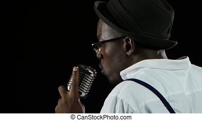 Singer the view from the back holding his microphone and gesticulating hands sings. Black background. Close up