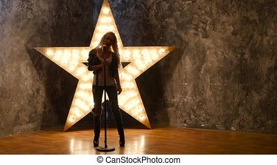 singer with blonde curly hair, microphone, dances. shining star in the background. slow motion, silhouette