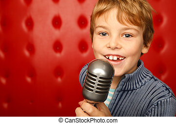 Singing boy with microphone on rack against red wall. Close ...