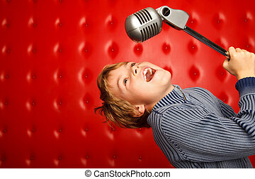 Singing boy with microphone on rack against red wall. ...