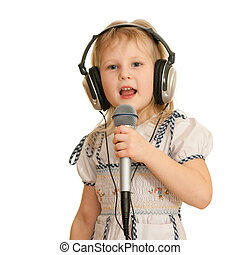 A cheerful little girl in headphones holding a microphone is singing a song; isolated on the white background