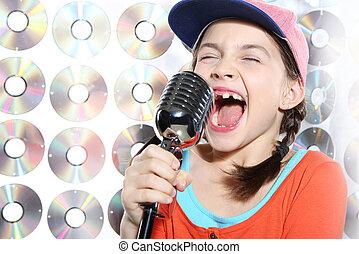 The girl singing karaoke wearing a baseball cap and orange shirt against the wall cd