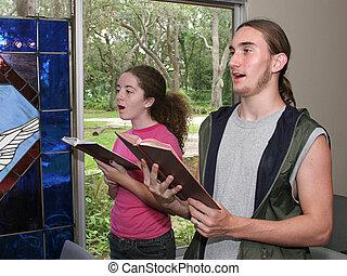 a teen boy and girl singing hymns in church.
