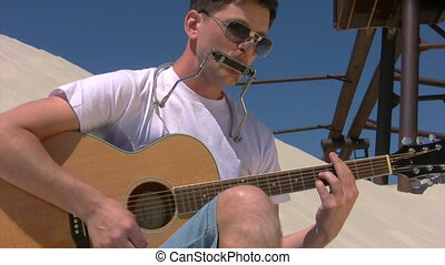 portrait of singing man in sunglasses with harmonica plays guitar on sandy beach