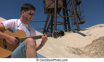 singing man in sunglasses with harmonica plays guitar on sandy beach