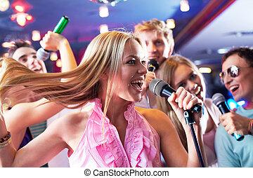 Singing - Portrait of joyous girl singing at party on...