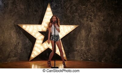 Singing Woman with Retro Microphone, shining star in the background, slow motion