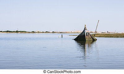Single and lonely sunken boat half-submerged in the estuary of Aveiro Lagoon, Portugal. Small quaint town in horizon.