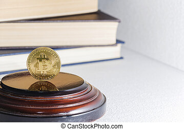 Single bitcoin coin or icon standing in sharp focus on a reflective surface with gold colored