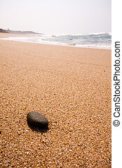 Single black rock lying on the beach