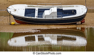 Single boat over the sand on low tide