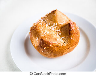 single brioche, French bun on a white plate and background