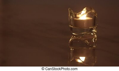 Single burning e-candle in a crystal candle holder.