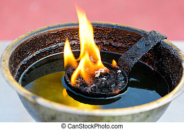 Single burning flame in a brass oil Lamp