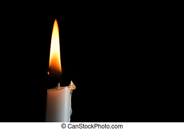 A single white candle burns shining into the darkness with nice text space.