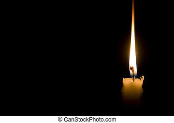 single candle light on black background