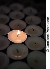 Single candle lighting in the dark
