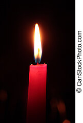 Single candle on a black background
