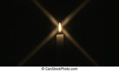 Wide shot of a single candle burning in the dark