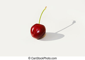 Single cherry against white background with shadow