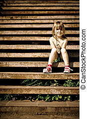 Single child is sitting on the stairs. Crossprocess.