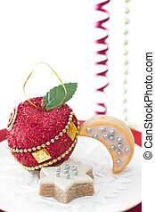 Single Christmas decoration in shape of red apple with couple of cookies on white background