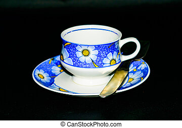 Single coffee cup on the plate with spoon