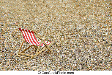 deck chair - single deck chair on a deserted pebbled beach