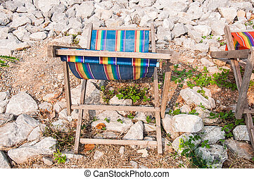 Single deck chair on a many stone