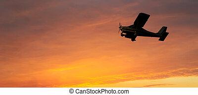 single engine flying at sunset