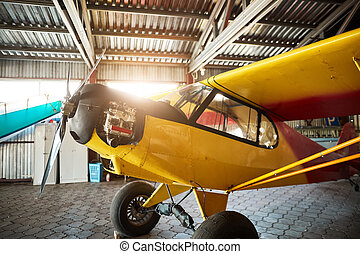 single-engine propeller airplane standing in hangar with opened motor cabinet