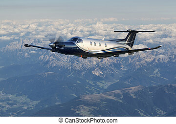 Single-engine turboprop aircraft flying over the Alps in...