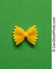 single uncoocked farfalle pasta on green background