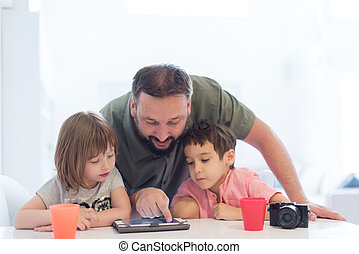 single father at home with two kids playing games on tablet