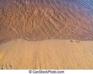 Single footprint in the sand on the beach near the waves