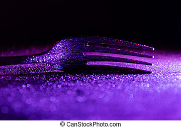 Single fork with waterdrops, in the dark illuminated with colourful gradient LED light.