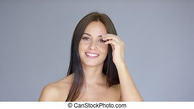 Single gorgeous young adult woman holding hand behind her head over gray background with copy space